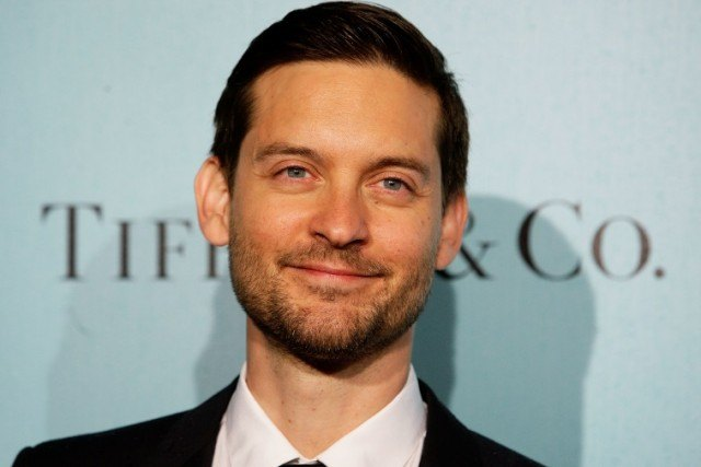 Tobey Maguire smiles while posing in front of a blue wall.