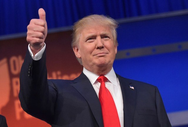 Donald Trump on stage with a thumbs-up.