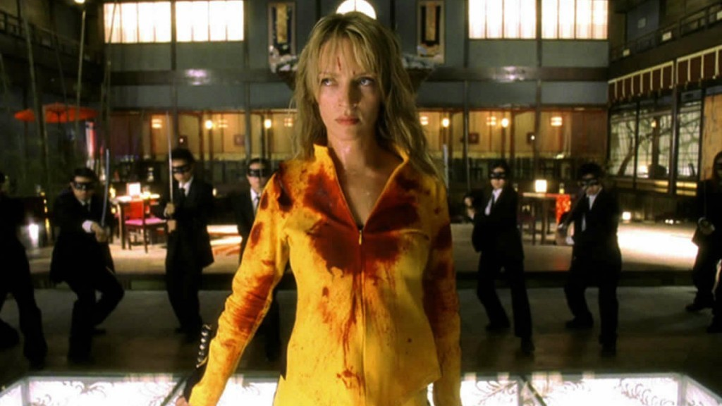 The Bride stands in a blood-covered yellow jump suit surrounded by men in suits.