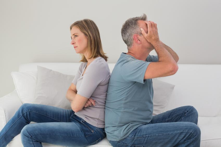 an older couple sitting back to back in frustration