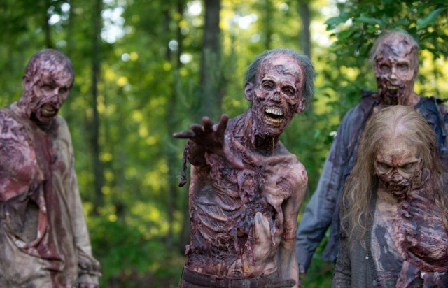 Four zombies in the forest in a scene from AMC's 'The Walking Dead'