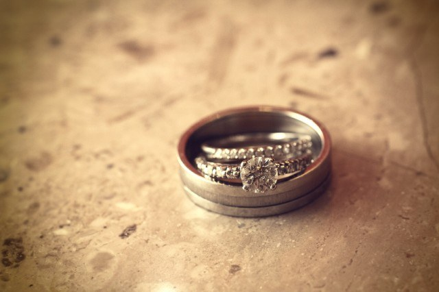 A wedding ring placed on a wooden surface.