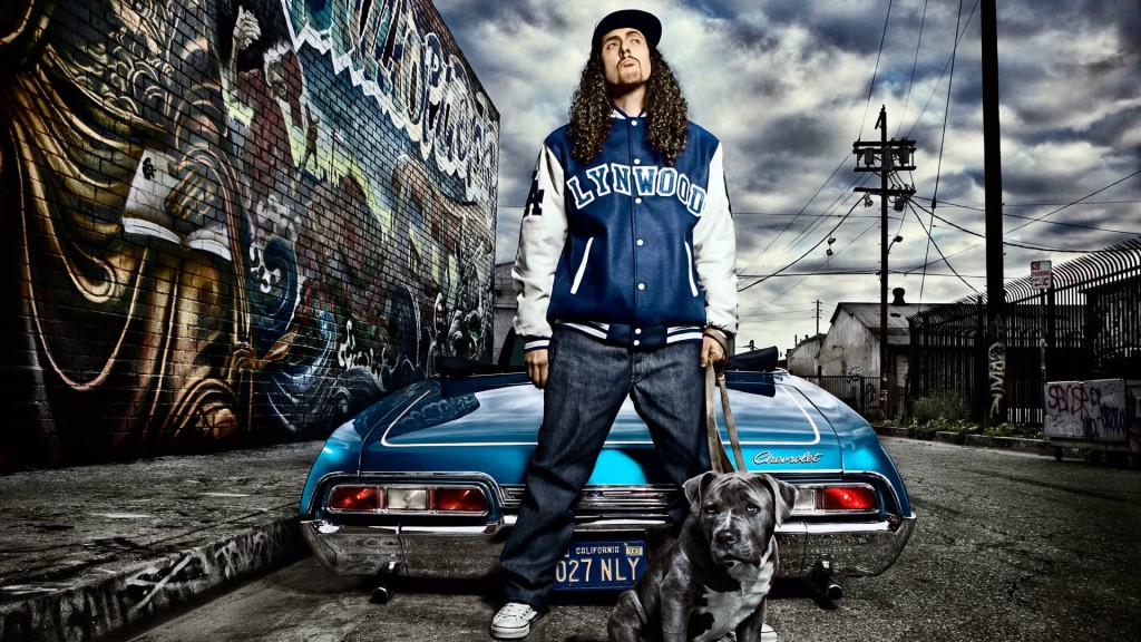 Weird Al Yankovic stands in front of a car and wall covered in graffiti. He is also holding a leash to a pitbull.