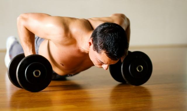 close-up of a man performing push-ups with dumbbells