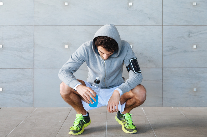 Young man resting on a run, drinking a sports drink