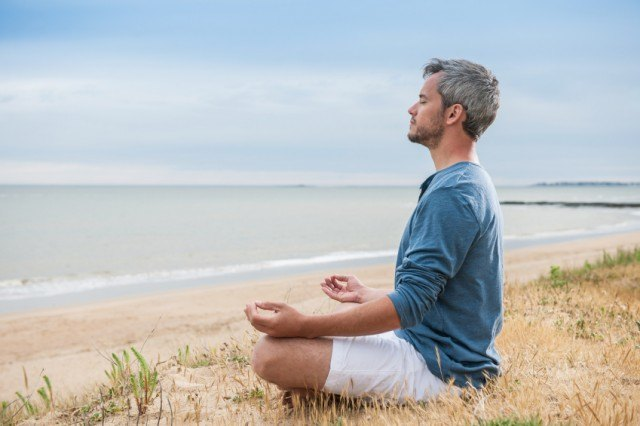 A man meditating on the beach for relaxation