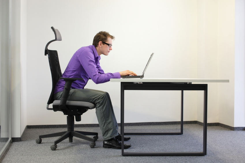 Man slouching over computer
