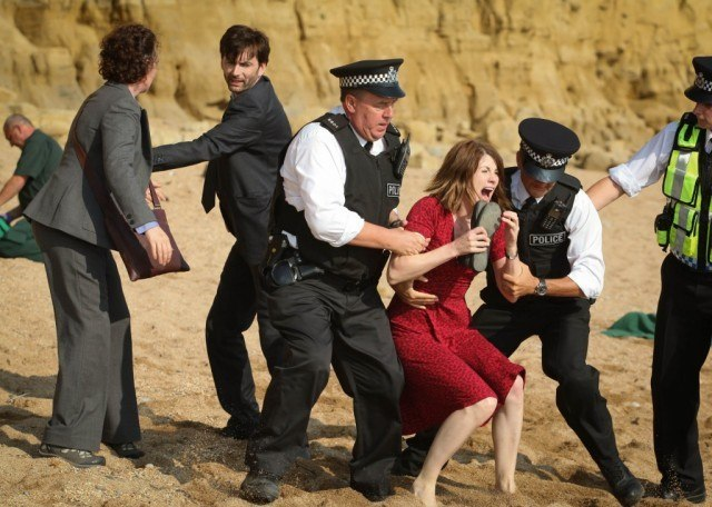 Two police officers drag a screaming Beth Latimer away from the crime scene as Detectives Benson and Hardy stand nearby in a scene from the first episode of 'Broadchurch.'