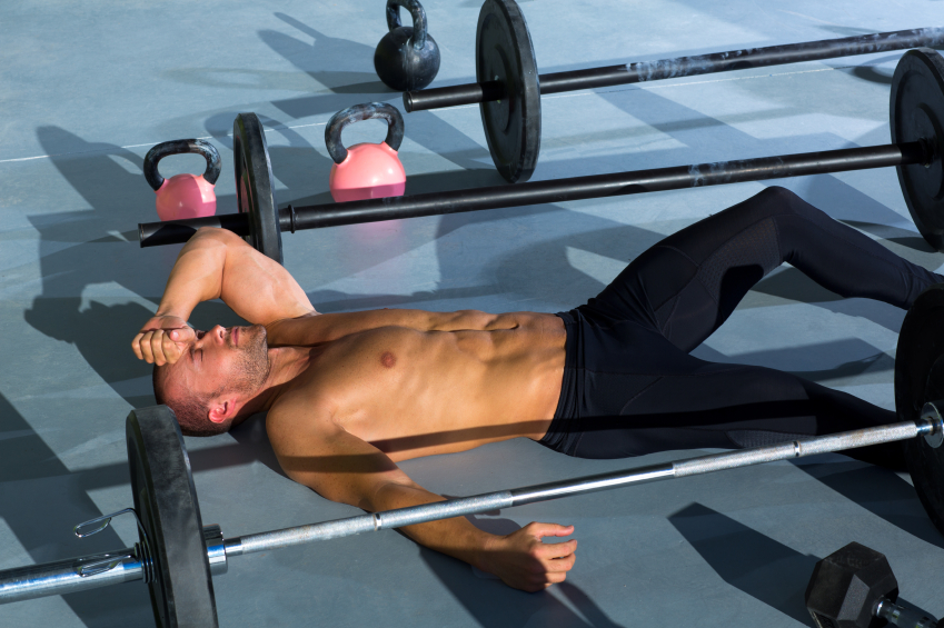 exhausted man at the gym who is weight lifting