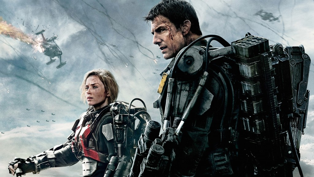 Emily Blunt and Tom Cruise stand next to each other in armor as helicopters fly overhead in Edge of Tomorrow