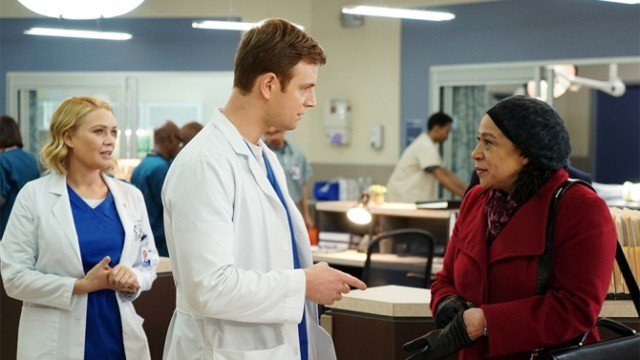 A team of doctors speaks to a woman in a red jacket.
