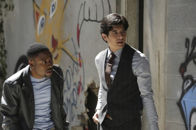Justin Hires and Jon Foo crouch near a wall of graffiti in Rush Hour