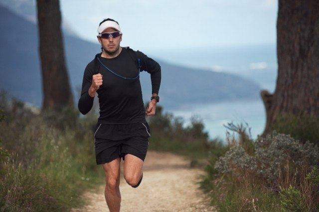 Fitness man running down a trail