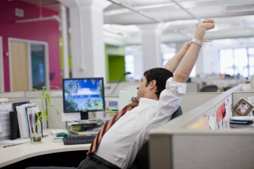 Businessman stretching at work desk