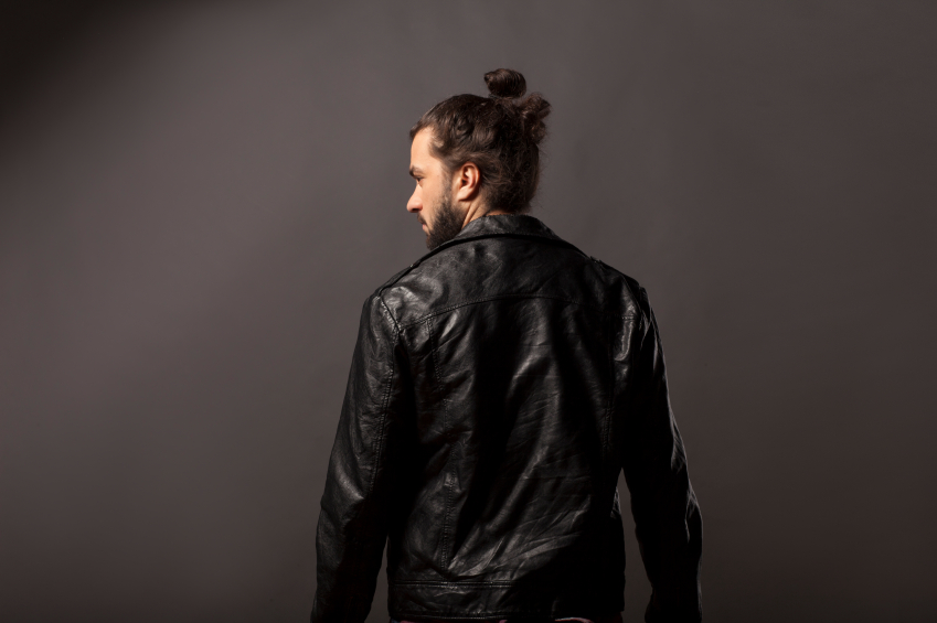 a man with a bun wearing a leather jacket