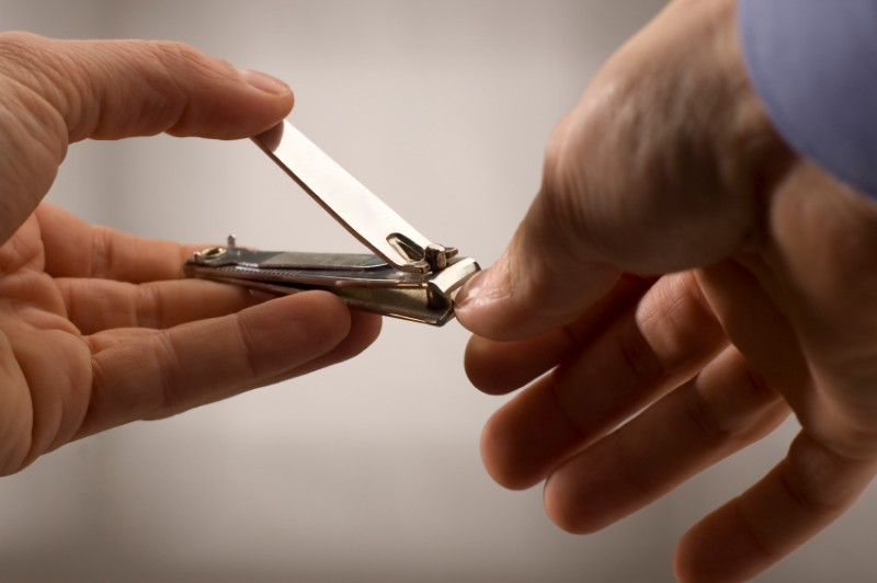 man clipping fingernails with nail clipper