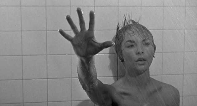 Marion reaching forward while in the shower.