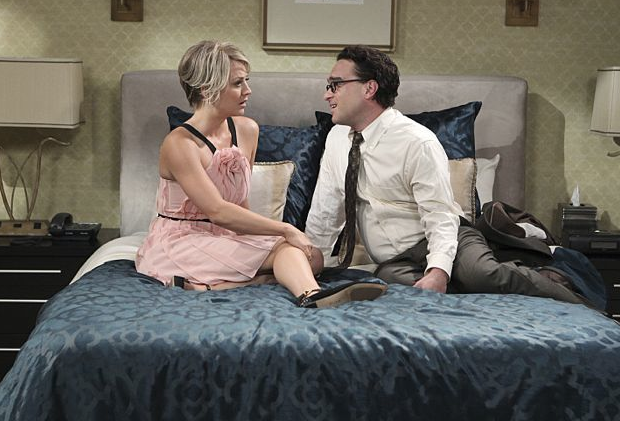 Kaley Cuoco as Penny and Johnny Galecki as Leonard on The Big Bang Theory sitting on a bed