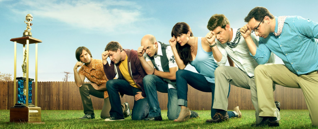 Jon Lajoie as Taco, Mark Duplass as Pete, Paul Scheer as Andre, Katie Aselton as Jenny, Stephen Rannazzisi as Kevin, and Nick Kroll as Ruxin kneeling in the grass next to a trophy on The League