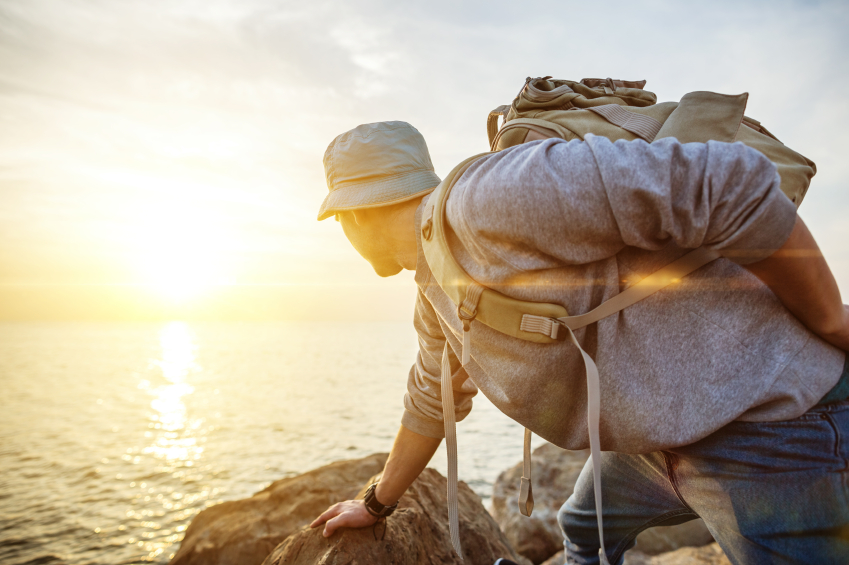 Man climbing rocks at sunset