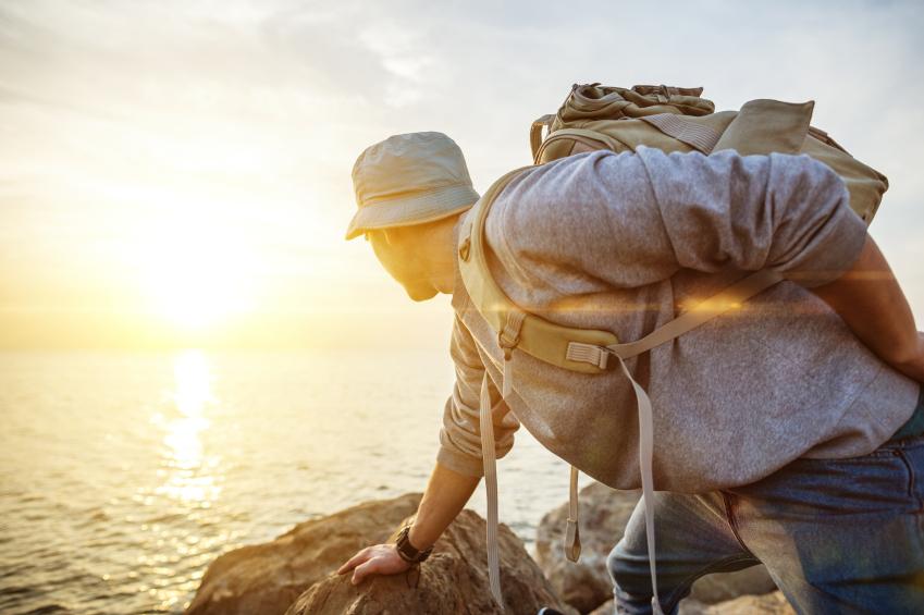 Man climbing rocks at sunset.