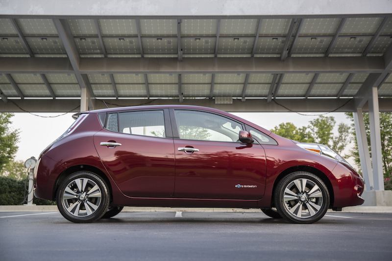 Side view from passenger side of red 2016 Nissan Leaf