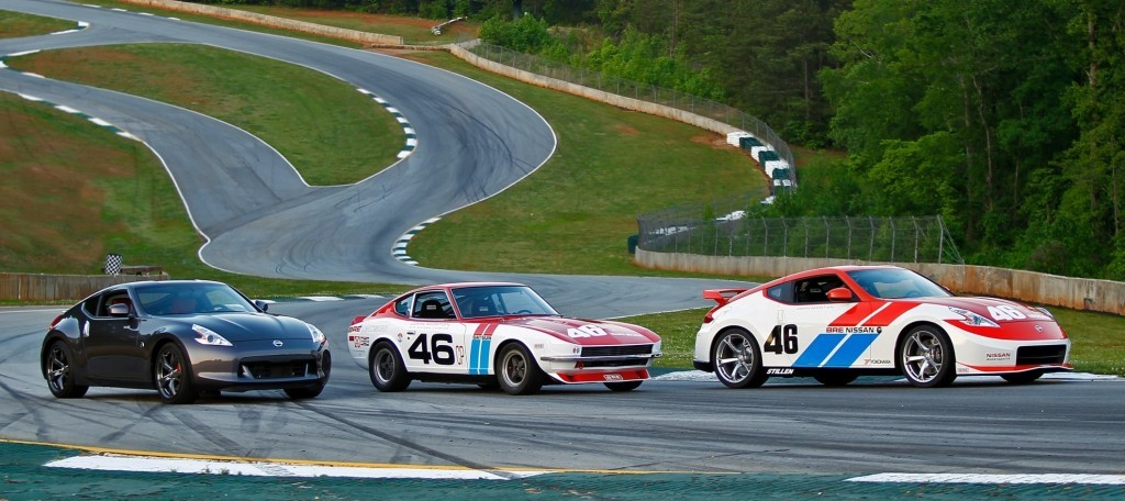 A Datsun 240Z and Nissan 370Z parked on a race track.