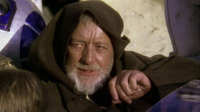 Alex Guiness wearing a brown cloak with a hood, speaking and looking upwards