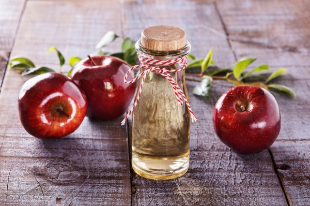 Vinegar in a vial surrounded by apples on a wooden table.