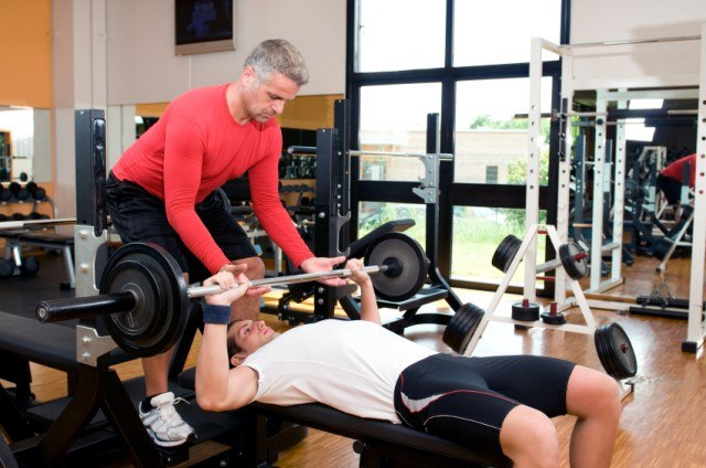 Man being spotted while doing bench press