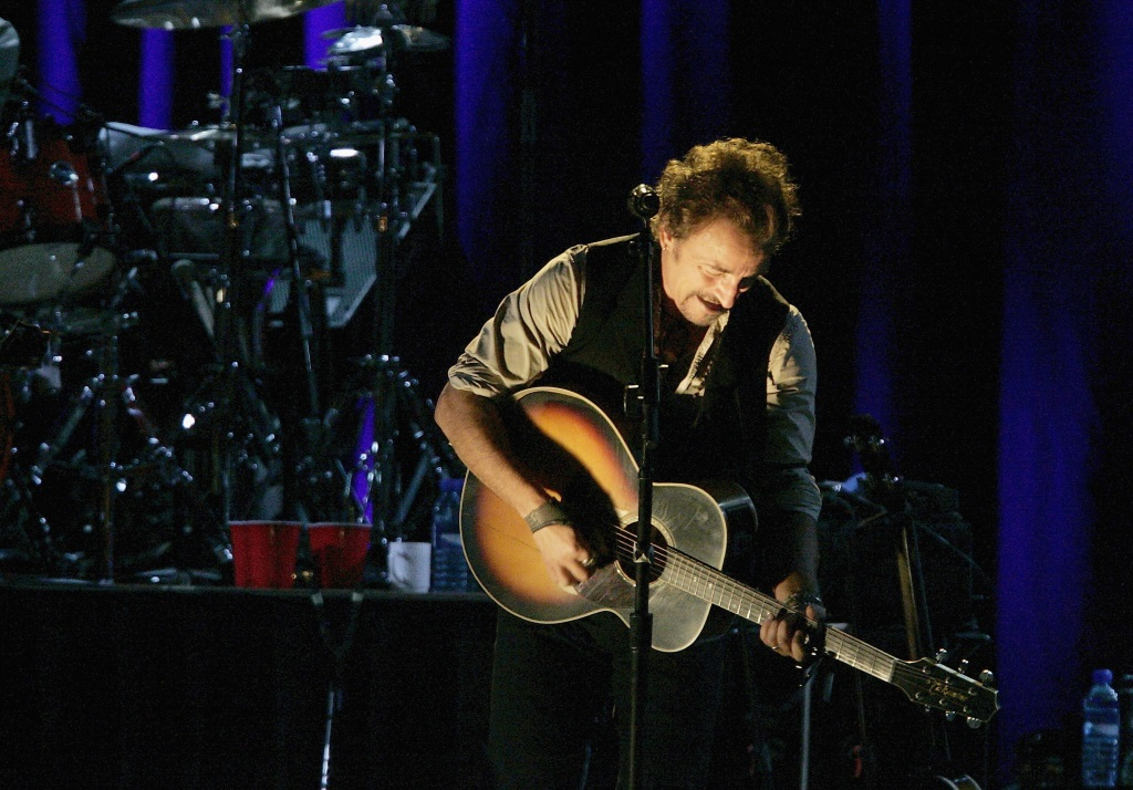 Bruce Springsteen is performing on stage with a guitar.