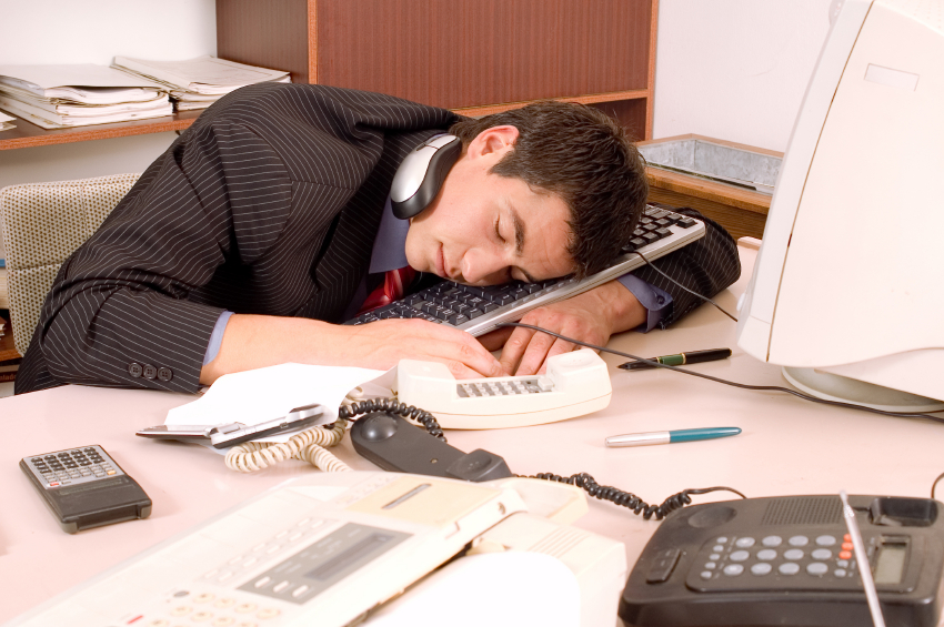 A man sleeping at his desk
