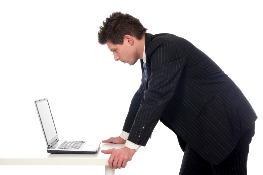 man standing at his desk and working
