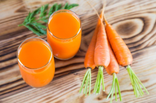 juice and carrots on table