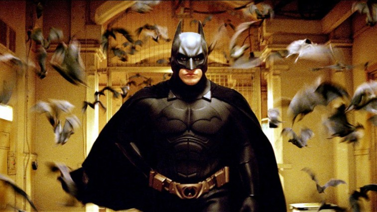 Christian Bale in the Batsuit surrounded by bats in Batman Begins