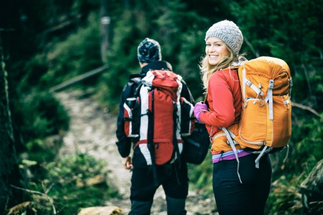 Couple with backpacks hiking in the mountains
