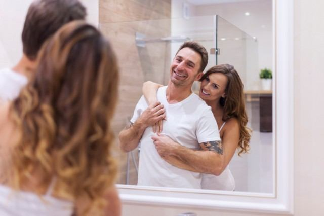 couple laughing in front of bathroom mirror