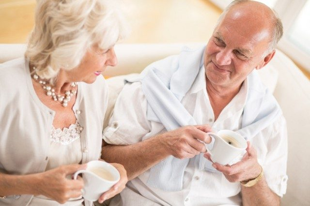 an elderly couple drinking coffee together