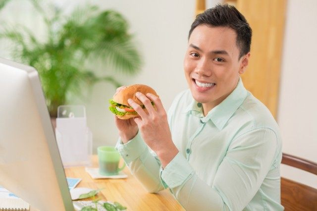 man relaxing and enjoying a burger