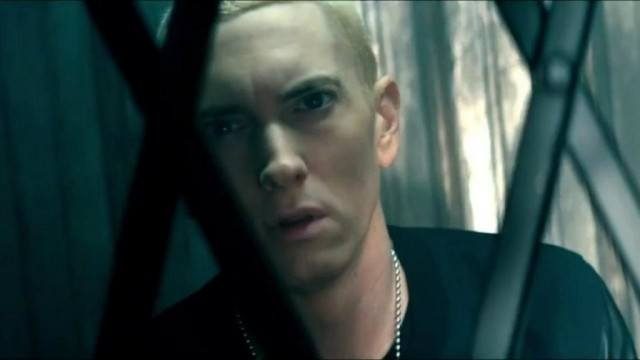 Eminem looks at the camera behind a gate.
