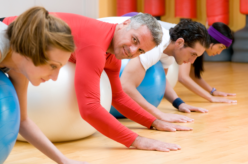 people doing stability ball exercises in a class