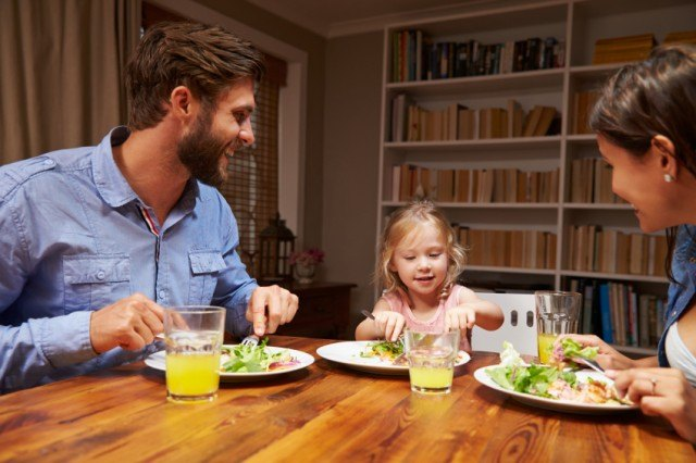 Family enjoying dinner with child.