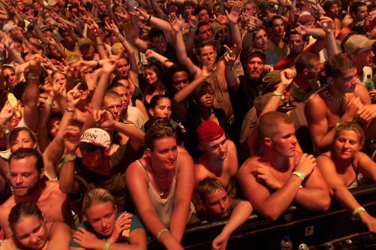 The concert goers are waving their arms in the air.