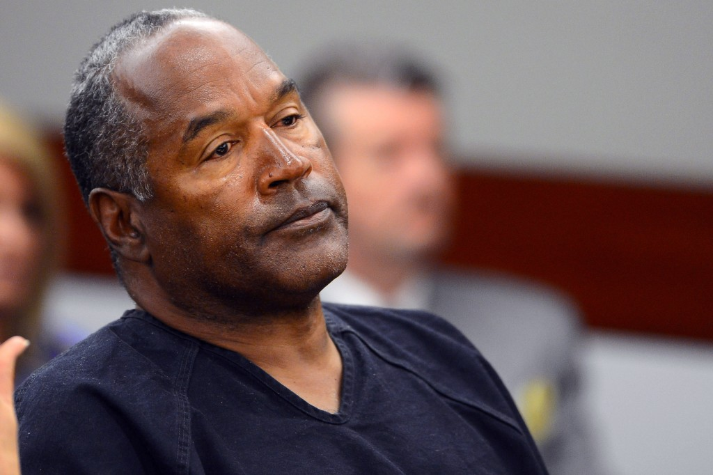OJ Simpson wearing a blue prison suit, sitting in a courtroom with his head tilted back slightly