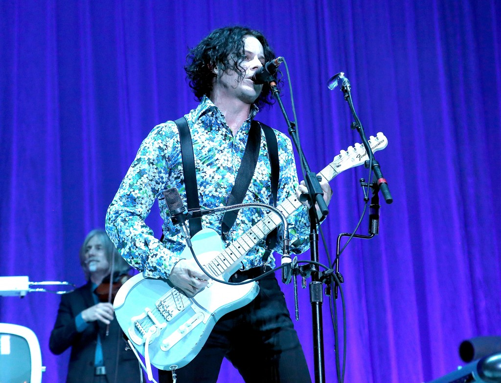 Jack White is playing guitar and singing on stage.
