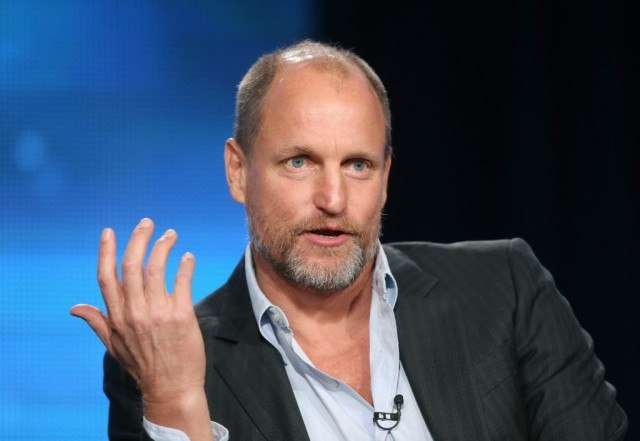 Woody Harrelson holds up his hand while speaking at a panel
