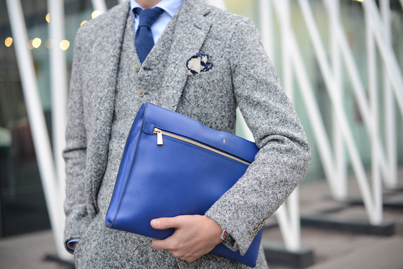man wearing a suit and holding a clutch