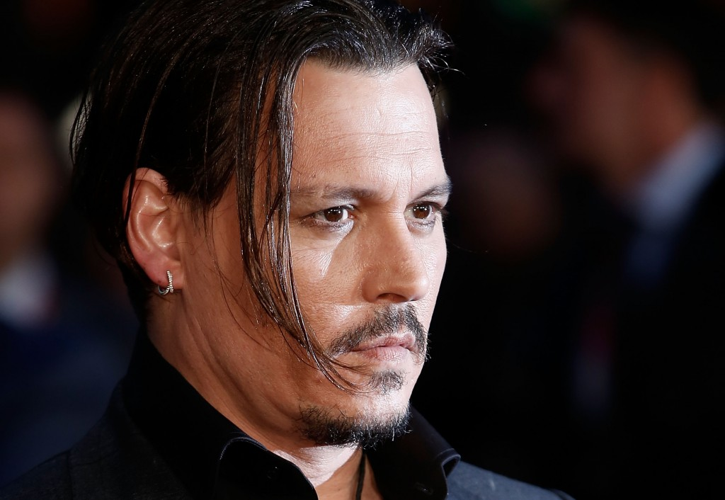 Johnny Depp with a lock of long hair hanging over his face, looking to the right of the frame