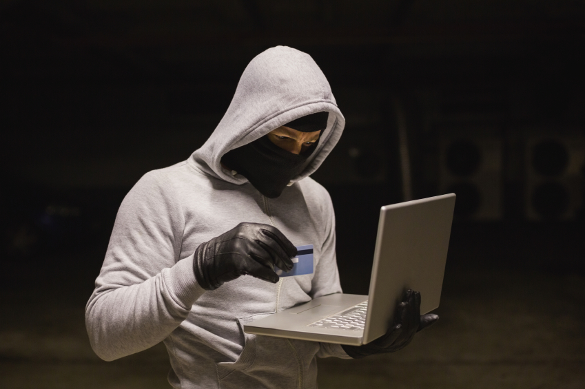 Hacker with credit card and laptop