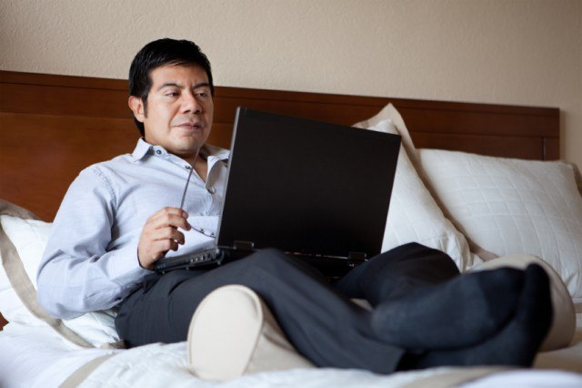 man sending emails in bed